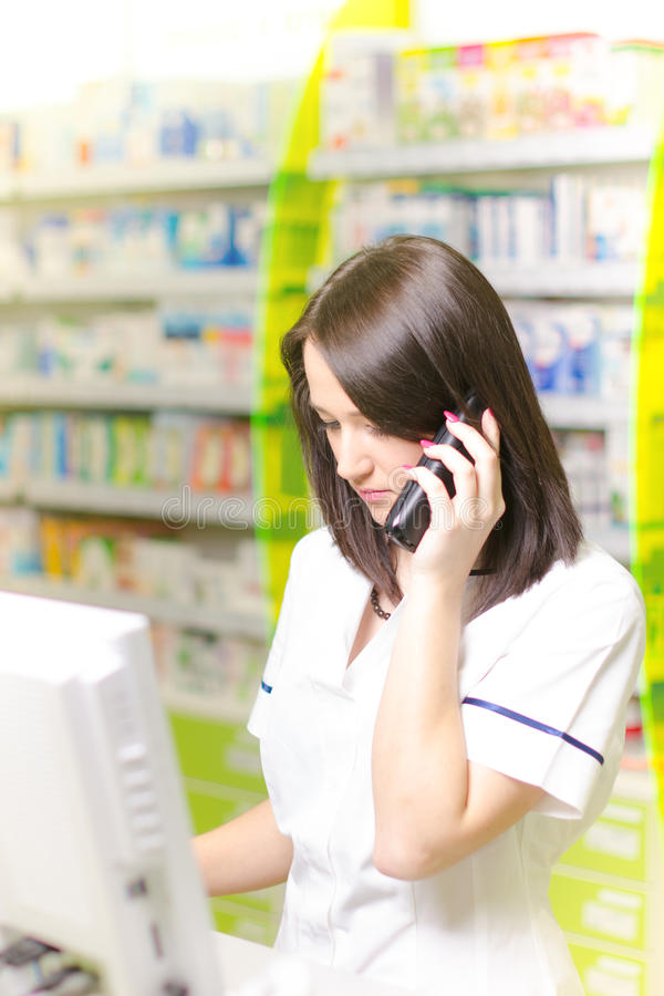 Young pharmacist woman expressing wonder while having a phone call. Pharmaceutical background. Drugstore. Pills and medicine. Young pharmacist woman expressing royalty free stock image