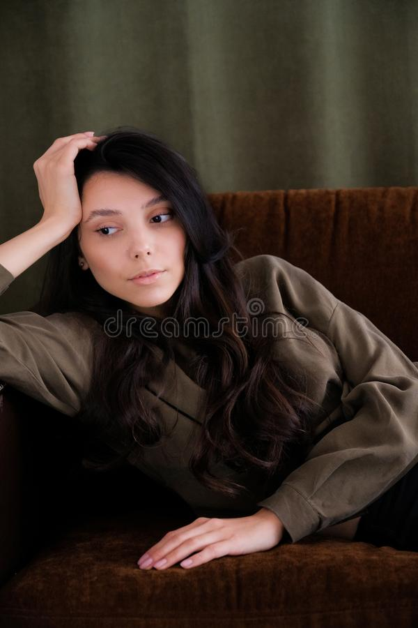 A young photogenic portfolio girl or model is lying on the couch looking away or down with a calm relaxed look. The concept of royalty free stock photography