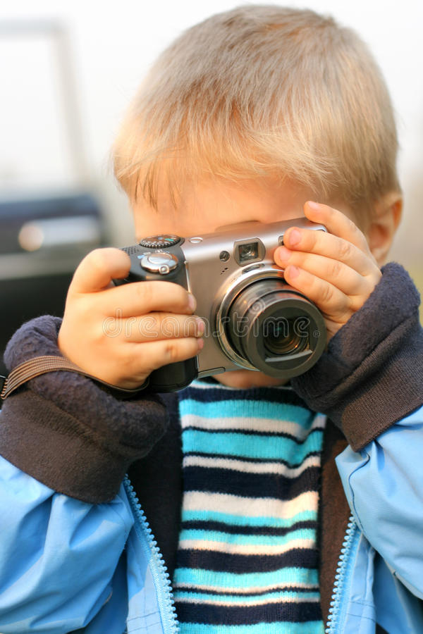 Young photographer. Little boy gets ready to take a photograph royalty free stock photography