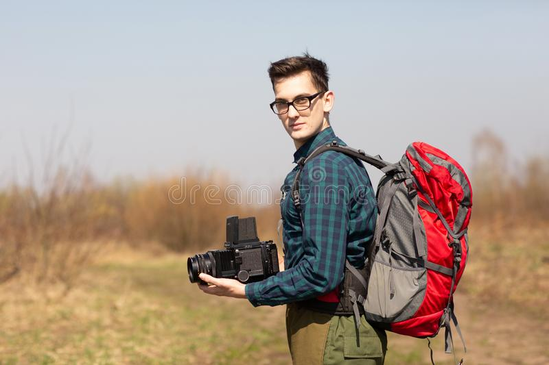 Young photographer with a backpack and a vintage camera in search of picturesque places royalty free stock image