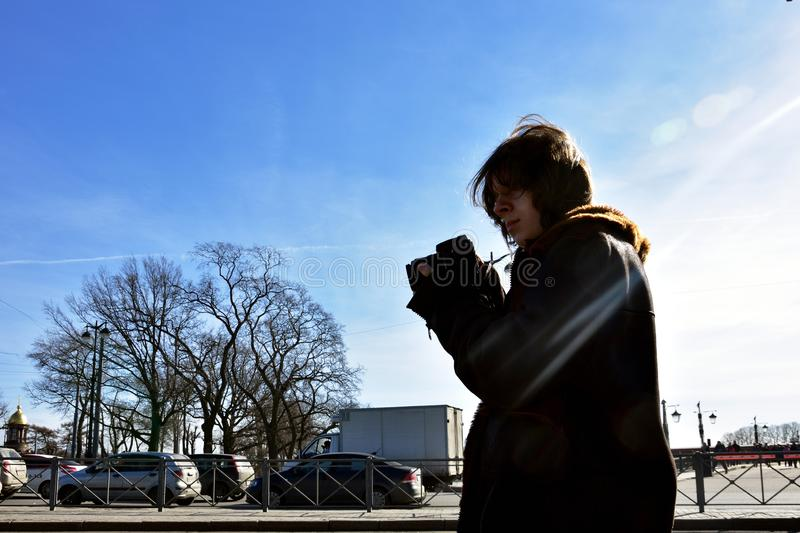 Young photogropher is shooting on the streets, Saint-Petersburg, Russia royalty free stock images