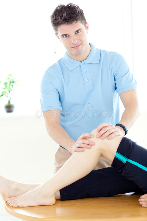Young physical therapist giving a leg massage royalty free stock photography