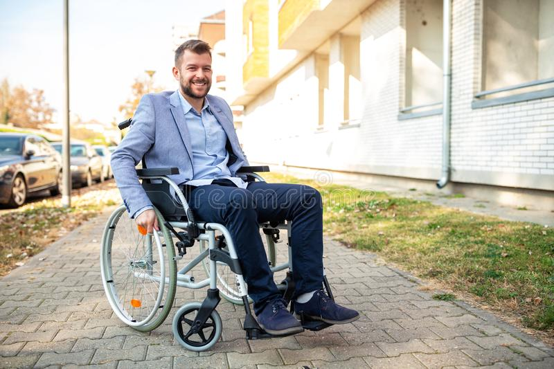 Young physically challenged man in his wheelchair stock photography