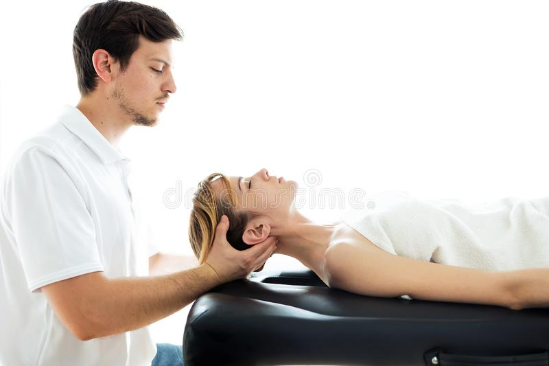 Young physiotherapist doing a neck treatment to the patient in a physiotherapy room stock images
