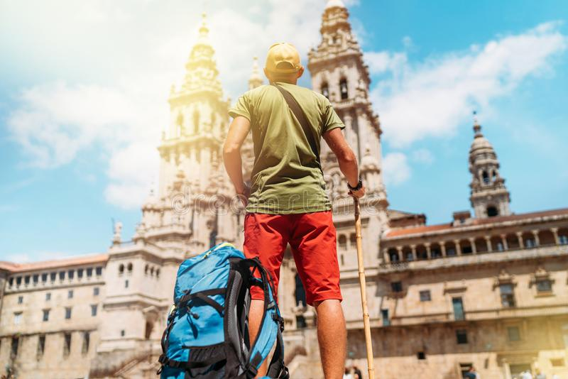 Young pilgrim backpacker man standing on the Obradeiro square plaza - the main square in Santiago de Compostela as a end of his stock image