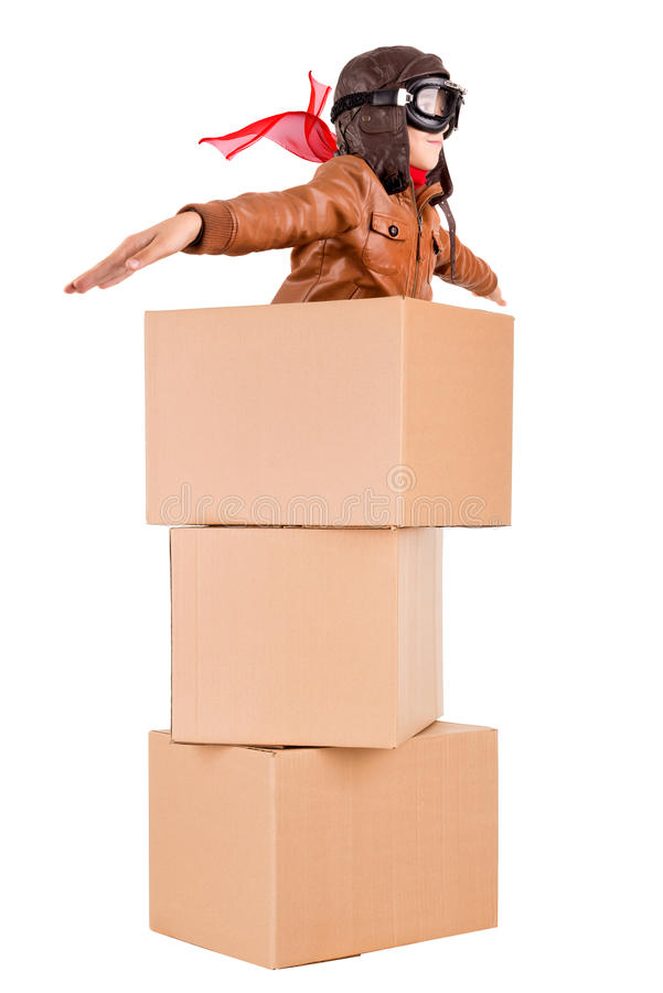 Young pilot. Young boy pilot flying a cardboard box isolated in white stock image