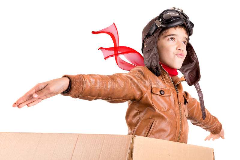Young pilot. Young boy pilot flying a cardboard box isolated in white stock photography