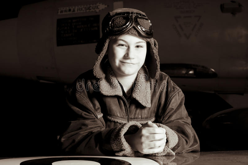 Young Pilot smiling at camera. A confident young pilot in flight jacket / hat / goggles is smiling at the camera stock photos