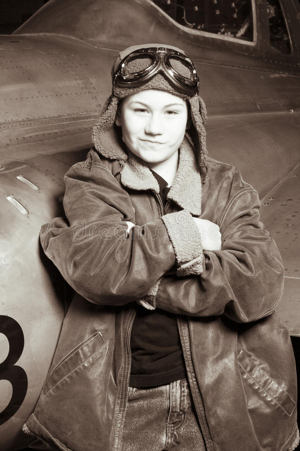 Young Pilot smirking at camera. A confident young pilot in flight jacket / hat / goggles is leaning against a jet and smirking at the camera stock image