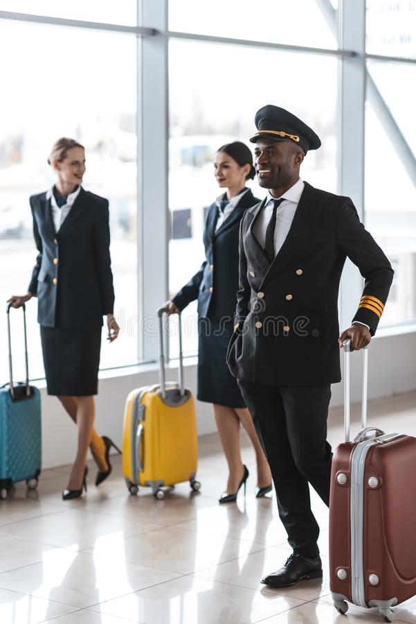 young pilot and stewardesses with luggage walking royalty free stock images
