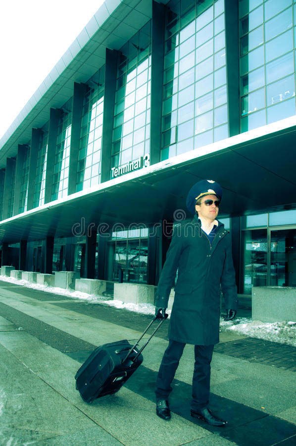 Young pilot walking with baggage in Kastrup airpor royalty free stock photo