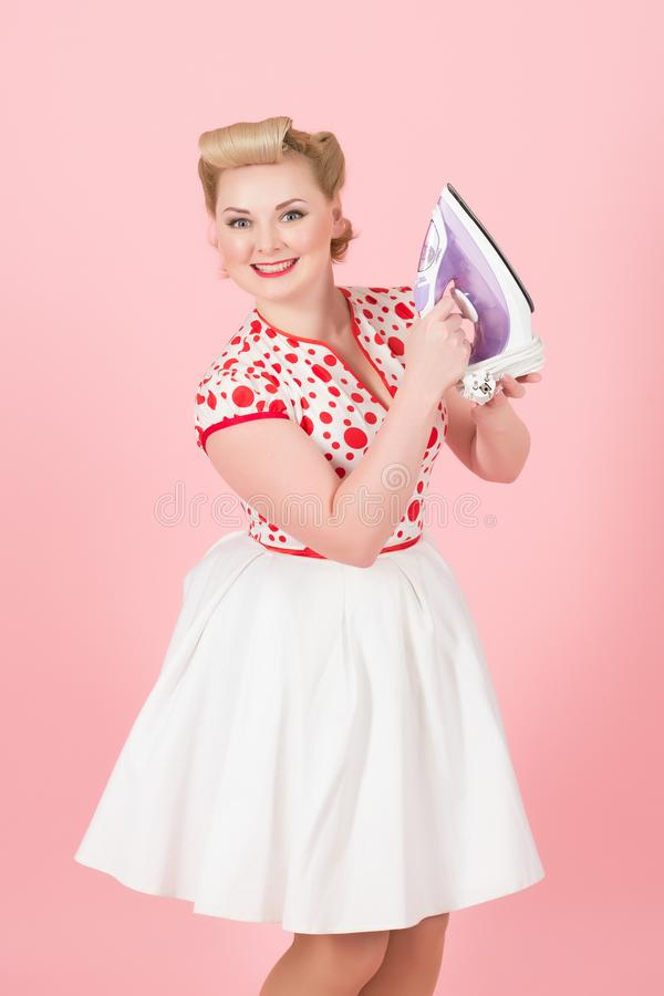 Young pin-up styled girl holds iron on pink background. Beautiful pin-up blonde woman with curls prepare iron for work isolated in studio. Blonde lady happy to stock photography