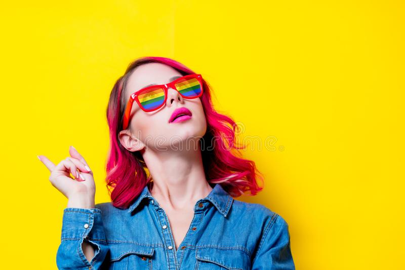 Young pink hair girl in blue shirt and rainbow glasses stock photography