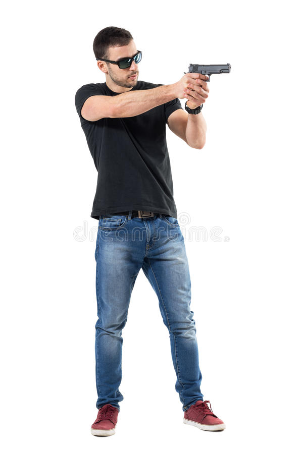 Young plain clothes policeman with sunglasses aiming gun away. Side view. stock photography