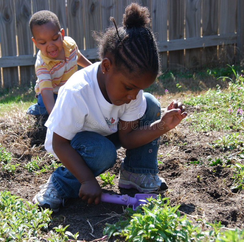 Young Planters. Two young children are working out in the garden. One child is pulling weeds while the other is planting flowers stock photos