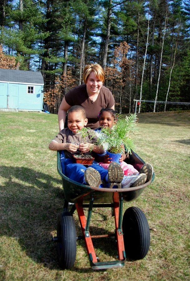 Young Planters. A mother is pushing her children in a wheel barrel as they plant the garden