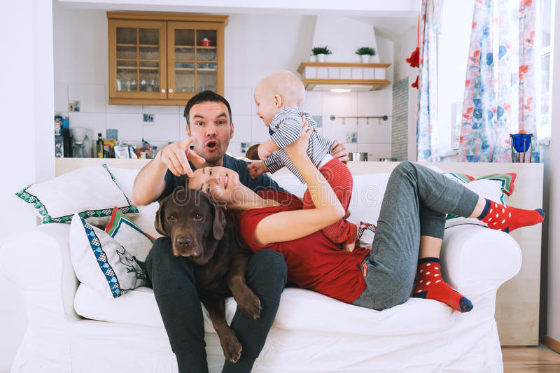 A young playful family at home on the couch. royalty free stock photography