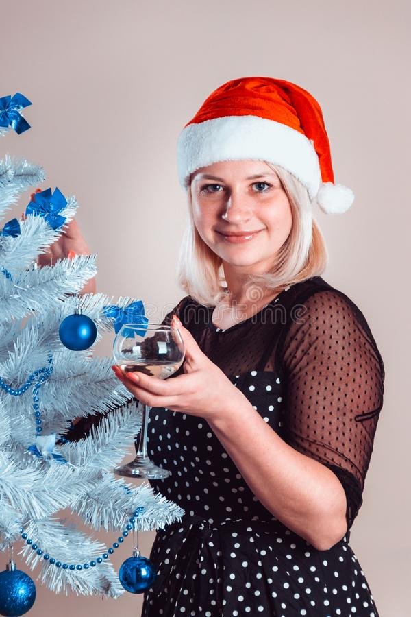 Young pleasant happy woman with glass of champagne in hand stands. Near white artificial Christmas tree with blue ball toys. Cheerful girl in red cap and stock photo