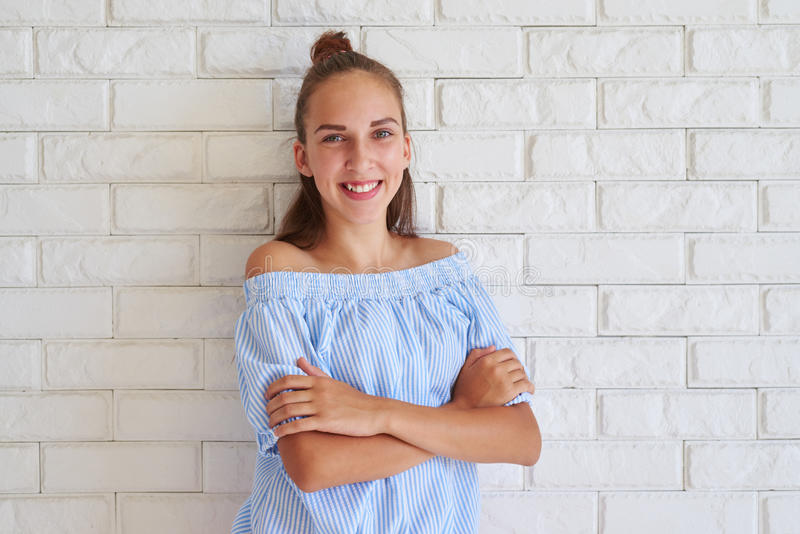 Young pleased girl folded her arms while standing against white. Wall royalty free stock photos