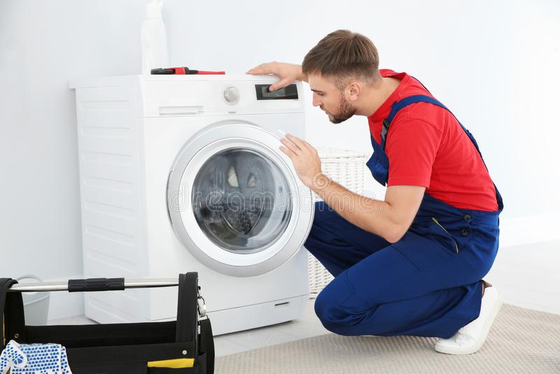 Young plumber examining washing machine stock photos