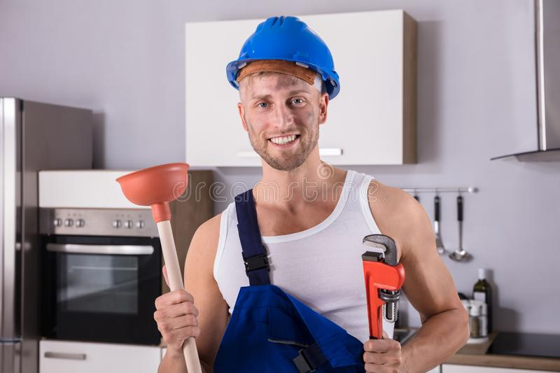 Young Plumber Holding Wrench And Plunger In Kitchen. Portrait Of A Smiling Young Plumber Holding Wrench And Plunger In Kitchen At Home royalty free stock photos
