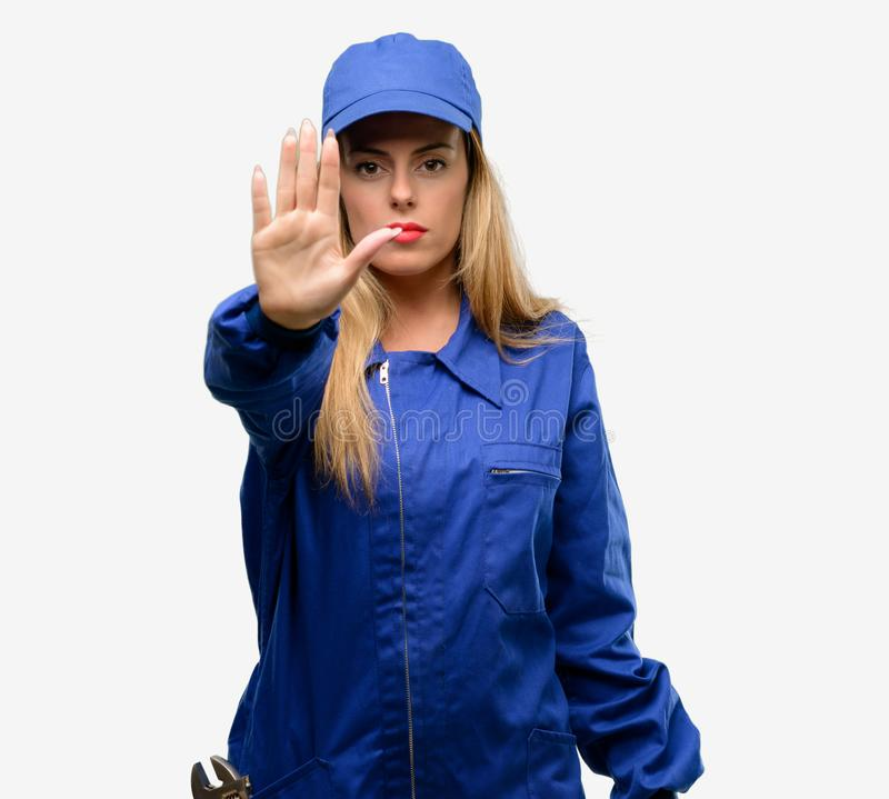 Young woman with plumber clothes isolated over grey background royalty free stock photos