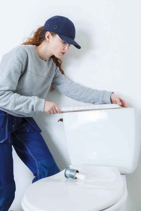 Young plumber woman near flush toilet royalty free stock photography