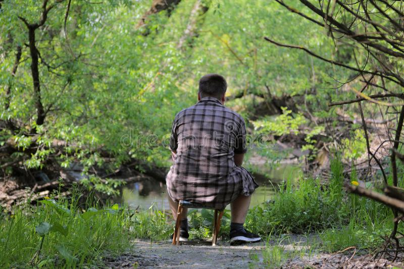 A young plump man sits on a small folding chair with his back to the camera. Sitting on the banks of the river watching the water. In the park among the bright royalty free stock photo