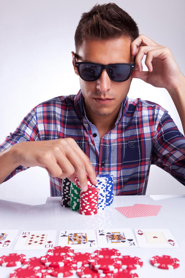 Young poker player raises the bet stock image
