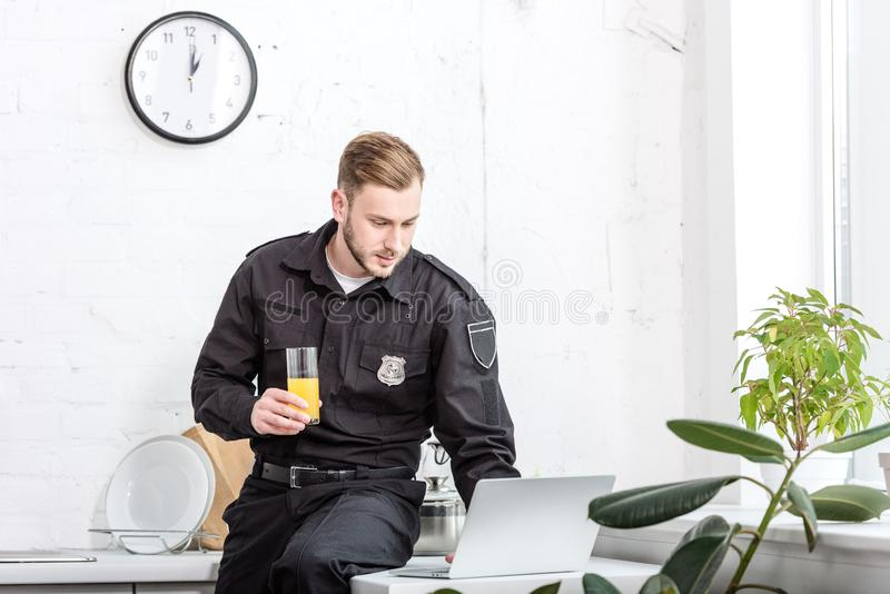 Young police officer sitting on table with glass of orange juice and using laptop. At kitchen royalty free stock photos