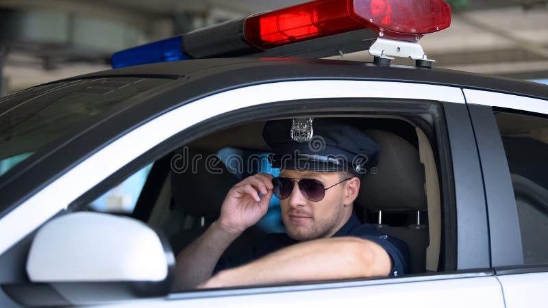 Young policeman adjusting sunglasses sitting in patrol car, responsible job. Stock photo royalty free stock image