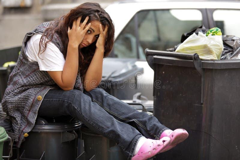 Young poor girl in bin stock photos