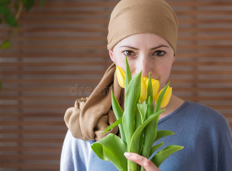 Young positive adult female cancer patient holding bouquet of yellow tulips, smiling and looking at camera. royalty free stock photography