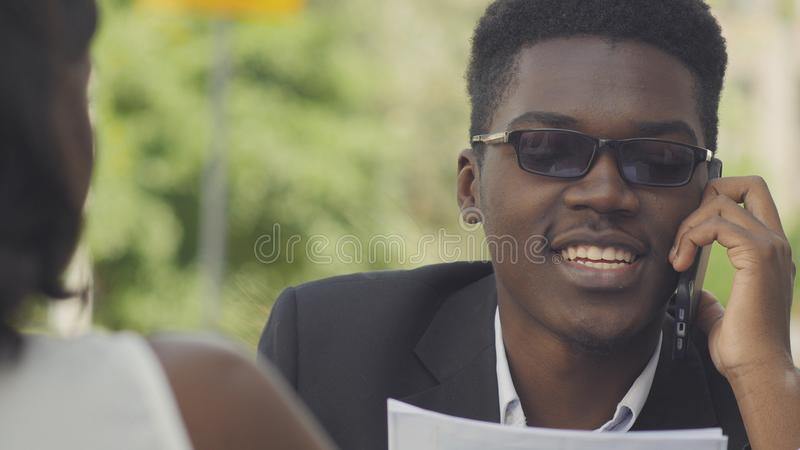 Young positive afro american entrepreneur in trendy eyewear having phone conversation with secretary assistant giving royalty free stock photo