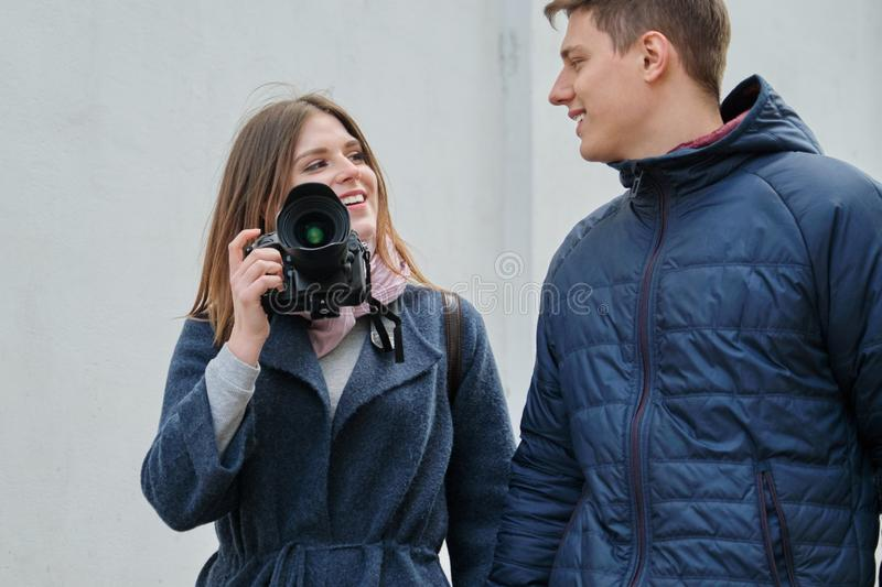 Young positive couple of young men and women blogger in city with camera. Travel, city blogging royalty free stock images