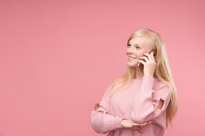 Young positive girl talking on mobile pink background. pleasant communication and communication. Beautiful blond cute smiling talking on smart phone royalty free stock images