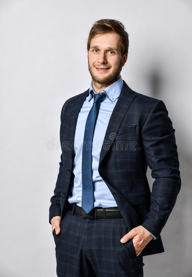 Young positive handsome business man in official costume suit and tie standing and smiling over light grey wall royalty free stock photos