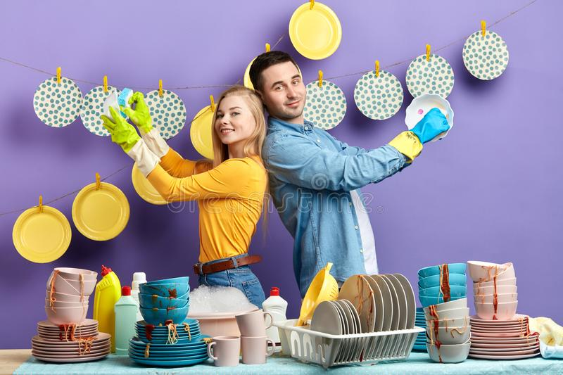 Young positive happy couple standing back to back and washing dishes stock photos