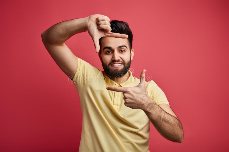 Young positive male in yellow T-shirt making frame with his hands royalty free stock image