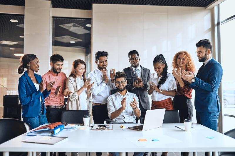 Young positive people applauding in the office stock image