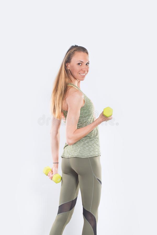 Young positive smiling woman working out with weights stock images