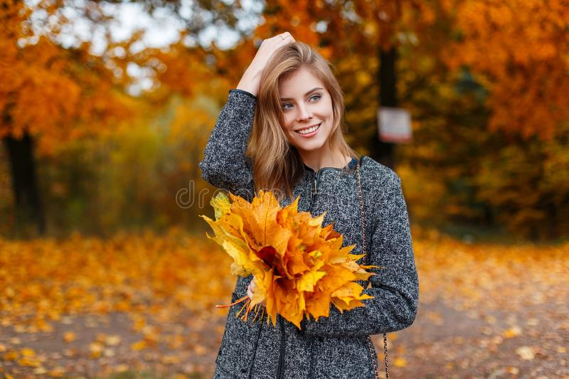 Young positive young woman with a beautiful smile in a fashionable gray coat with a bouquet of autumn yellow-gold leaves stock image