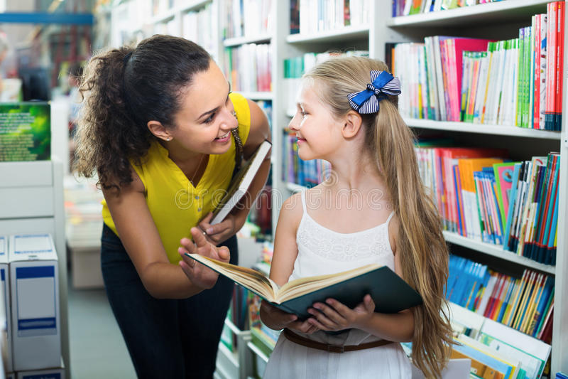 Young positive woman with child in bookstore stock photo