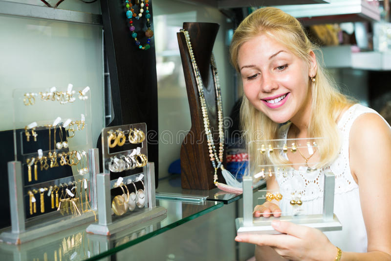 Young positive woman picking box with earrings royalty free stock photos