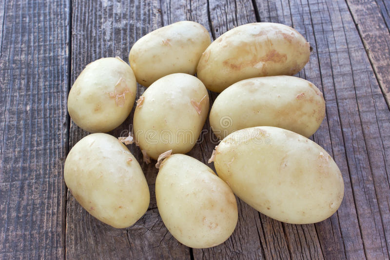 Young potatoes on wooden background stock images