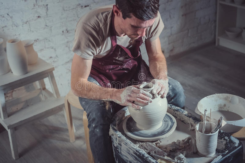 Young potter. Young man on a potter`s wheel stock photos