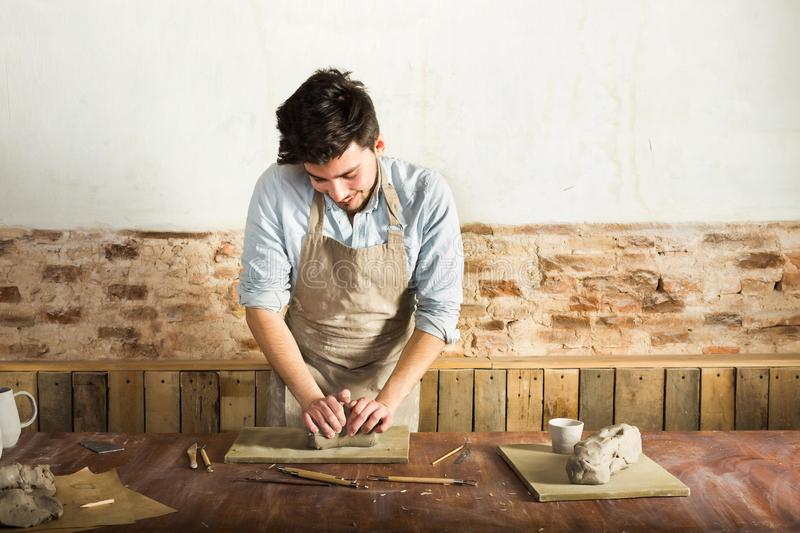 A young potter wearing apron and shirt kneading the clay on the desktop. Front view. Art and business, hobby and. A young potter wearing apron and shirt kneading stock photo