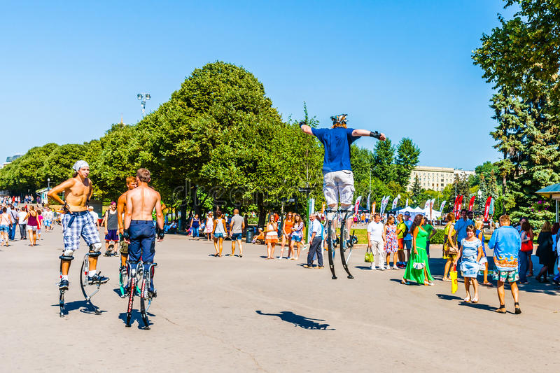 Young power jumpers on jumping stilts in Moscow Gorky park. Moscow, Russia. 27th July 2014: Young power jumpers on jumping stilts in Moscow Gorky park. This stock image