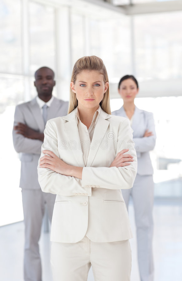 Young Powerful looking business woman. Looking at camera arms folded in fromt of her businessteam royalty free stock photos