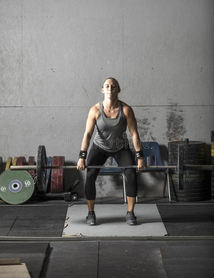 Young powerful woman lifting heavy weights in gym stock images